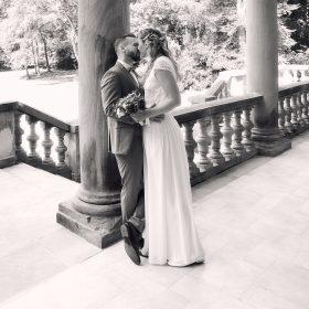 Schwarzweissfoto vom küssenden Brautpaar auf der Steinterrasse mit hohen Säulen - Schloss Eldingen © Hochzeitsfotograf www.hochzeitsverliebt.de