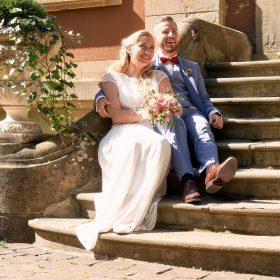 In der Sonne sitzt das Hochzeitspaar lachend auf der hellen Steintreppe- Schloss Eldingen © Hochzeitsfotograf www.hochzeitsverliebt.de