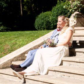 Die Braut genießt  mit ihrem Mann auf den Stufen im Freien die Sonne - Schloss Eldingen © Hochzeitsfotograf www.hochzeitsverliebt.de