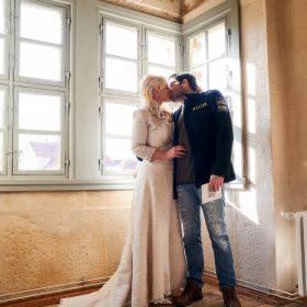 Das Brautpaar steht an den Fenstern beim Sonnenschein und küsst sich - Schloss Schöningen © Hochzeitsfotograf www.hochzeitsverliebt.de