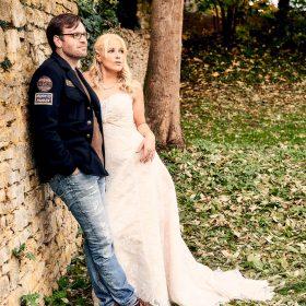 Das Brautpaar an einer Steinmauer im Grünen - Schloss Schöningen © Hochzeitsfotograf www.hochzeitsverliebt.de