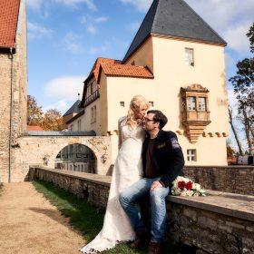 Auf der Mauer sitzendes Brautpaar mit Schloss und blauem Himmel im Hintergrund - Schloss Schöningen © Hochzeitsfotograf www.hochzeitsverliebt.de