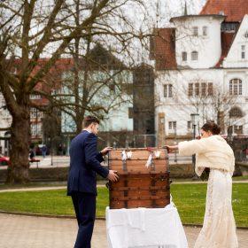 Brautpaar öffnet die Holzkiste mit Blick auf das Bomann Museum - Schloss Celle Hochzeit © Hochzeitsfotograf www.hochzeitsverliebt.de
