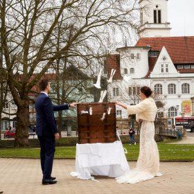Braut und Bräutigam sehen Tauben beim Flug aus der Holzkiste zu - Schloss Celle Hochzeit © Hochzeitsfotograf www.hochzeitsverliebt.de