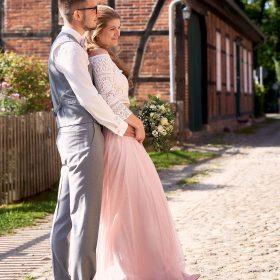 Braut im hellrosa Kleid schmiegt sich an ihren Bräutigam, der sie in seinen Armen hält - Kloster Wienhausen © Hochzeitsfotograf www.hochzeitsverliebt.de