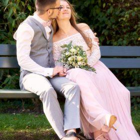 Der Bräutigam sitzt mit seiner Braut auf der grünen Bank und küsst sie auf die Wange - Kloster Wienhausen © Hochzeitsfotograf www.hochzeitsverliebt.de