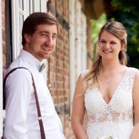 Die Braut lächelt zum Bräutigam, der am Fachwerk zwischen weissen Fenstern lehnt und in die Kamera schaut - Standesamt Winsen Aller © Hochzeitsfotograf www.hochzeitsverliebt.de