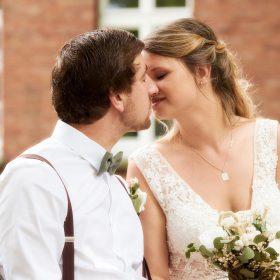 Das Brautpaar sitzt auf der Bank und küsst sich - Kirchengarten Winsen Aller © Hochzeitsfotograf www.hochzeitsverliebt.de