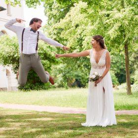 Der Bräutigam macht an der Kirche im Grünen einen Luftsprung in Richtung bei seiner Braut, die zu ihm zeigt - Kirchengarten Winsen Aller f © Hochzeitsfotograf www.hochzeitsverliebt.de