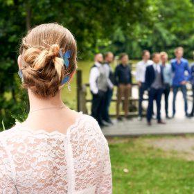 Braut mit blauen Schmetterlingen im Haar und Dutt schaut zum Bräutigam und seinen Freunden - Junkerhof Wittingen © Hochzeitsfotograf www.hochzeitsverliebt.de