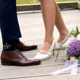 Hochzeitsschuhe vom Brautpaar an ihren Füßen auf dem Hozlsteg mit lilagrünem Brautstrauß - Junkerhof Wittingen © Hochzeitsfotograf www.hochzeitsverliebt.de