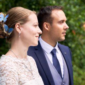 Braut in weiss und blauen Schmetterlingen im Haar mit Bräutigam im blauen Anzug und blaufabener Weste und Krawatte im Grünen - Junkerhof Wittingen © Hochzeitsfotograf www.hochzeitsverliebt.de