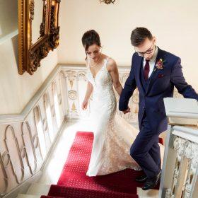 Brautpaar aus der Vogelperspektive beim Gang auf der Treppe mit rotem Teppich fotografiert - Celle Althoff Hotel Fürstenhof © Hochzeitsfotograf www.hochzeitsverliebt.de