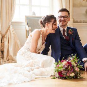 Sitzendes Brautpaar auf dem Boden im blauen Salon lacht in die Kamera - Celle Althoff Hotel Fürstenhof © Hochzeitsfotograf www.hochzeitsverliebt.de