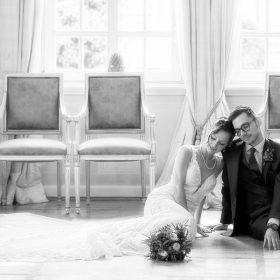 Das sitzende Brautpaar im blauen Salon auf dem Boden mit einer Stuhlreihe im Hintergrund als Schwarzweissaufnahme - Celle Althoff Hotel Fürstenhof © Hochzeitsfotograf www.hochzeitsverliebt.de