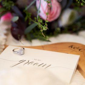 Silberner Ring auf cremefarbener Karte mit rosafarbenen Blumen und Holzbügel im Hintergrund - Celle Ringhotel Celler Tor © Hochzeitsfotograf www.hochzeitsverliebt.de