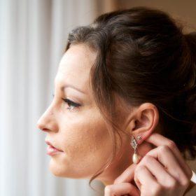 Die Braut mit braunem Haar und Hochtsteckfrisur steckt sich einen Ohrring an - Celle Ringhotel Celler Tor l © Hochzeitsfotograf www.hochzeitsverliebt.de