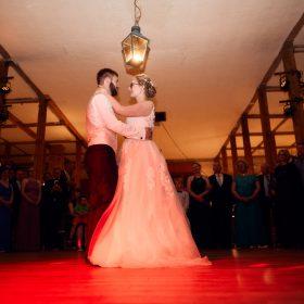 Brautpaar steht in der Hochzeitslocation und hält im roten Scheinwerfer den Eröffnungstanz - Hof Wietfeldt Bennebostel © Hochzeitsfotograf www.hochzeitsverliebt.de