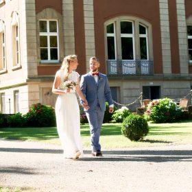 Hochzeitspaar schreitet am Schloss den Weg zur Trauung entlang - Schloss Eldingen © Hochzeitsfotograf www.hochzeitsverliebt.de