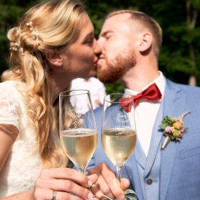 Das Brautpaar küsst sich im Sonnenschein und hält dabei die gefüllten Champagnergläser vor die Kamera - Schloss Eldingen © Hochzeitsfotograf www.hochzeitsverliebt.de