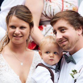 Das Brautpaar steht in der Gruppe ihrer Gäste mit ihrem Sohn zusammen und lächelt - Standesamt Winsen Aller © Hochzeitsfotograf www.hochzeitsverliebt.de