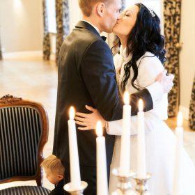 Stehendes Brautpaar küsst sich am Trautisch mit Kerzen im Vordergrund - Trauzimmer Schlösschen Bad Nenndorf © Hochzeitsfotograf www.hochzeitsverliebt.de