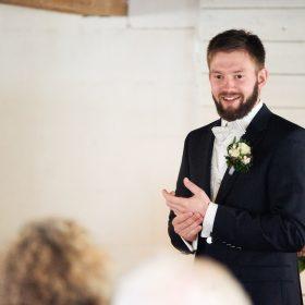 Bräutigam wartet in de Scheune vor weisser Holzwand lächelnd auf seine Braut - Hof Wietfeldt Bennebostel © Hochzeitsfotograf www.hochzeitsverliebt.de