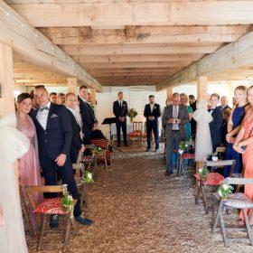 Blick in die gefüllte Scheune, bei der die Gäste stehend auf die Braut warten - Hof Wietfeldt Bennebostel © Hochzeitsfotograf www.hochzeitsverliebt.de