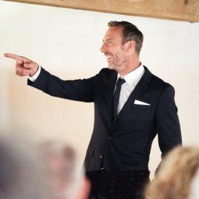 Trauredner im schwarzen Anzug zeigt lächelnd auf etwas - Hof Wietfeldt Bennebostel © Hochzeitsfotograf www.hochzeitsverliebt.de