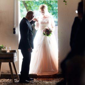 Die Braut schreitet mit Ihrem Vater durch die Scheunentür - Hof Wietfeldt Bennebostel © Hochzeitsfotograf www.hochzeitsverliebt.de