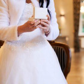 Die weiss gekleidete Braut im Anschnitt hält das weisse Ringkästchen in den Händen  - Trauzimmer Schlösschen Bad Nenndorf © Hochzeitsfotograf www.hochzeitsverliebt.de