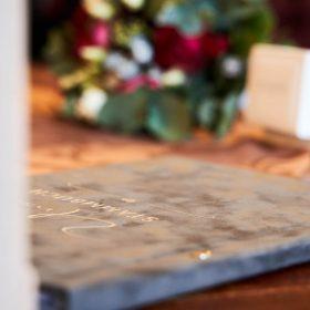 Detailaufnahme vom grausilbernen Samtstammbuch und dem rotgrünen Brautstrauß auf dem Tisch - Trauzimmer Schlösschen Bad Nenndorf © Hochzeitsfotograf www.hochzeitsverliebt.de