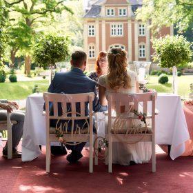 Brautpaar sitzt auf den weissen Traustühlen nah zusammen und hält sich die Hände  - Schloss Eldingen © Hochzeitsfotograf www.hochzeitsverliebt.de