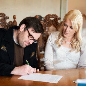 Der Bräutigam unterzeichnet das Eheversprechen mit einem grünen Stift - Trauzimmer Schloss Schöningen © Hochzeitsfotograf www.hochzeitsverliebt.de
