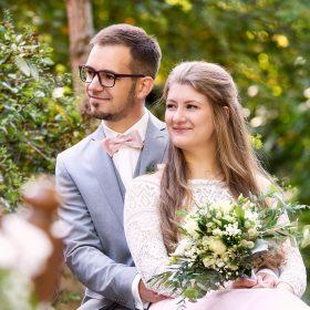 Das Hochzeitspaar sitzt im Grünen und schaut lächelnd in die Ferne - Kloster Wienhausen © Hochzeitsfotograf www.hochzeitsverliebt.de