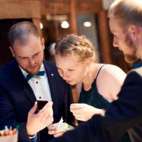 Drei Hochzeitsgäste in der Hochzeitslocation schauen gemeinsam in das Handy - Hof Wietfeldt Bennebostel © Hochzeitsfotograf www.hochzeitsverliebt.de