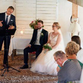 Trauender gestikuliert zum sitzenden Brautpaar während der Scheunenhochzeit - Hof Wietfeldt Bennebostel © Hochzeitsfotograf www.hochzeitsverliebt.de