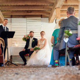 Sitzendes Brautpaar schaut während ihrer Scheunenhochzeit direkt zu den Gästen und in die Kamera - Hof Wietfeldt Bennebostel © Hochzeitsfotograf www.hochzeitsverliebt.de