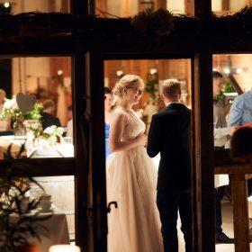Blick durch die Fachwerkbalken nach innen in die Hochzeitsfeier am Abend - Hof Wietfeldt Bennebostel © Hochzeitsfotograf www.hochzeitsverliebt.de