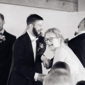 Lachende Szene mit dem Brautpaar während der Trauung als Schwarzweissaufnahme- Hof Wietfeldt Bennebostel © Hochzeitsfotograf www.hochzeitsverliebt.de