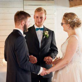 Trauzeugen hält die Hände des Brautpaares und hat gute Wünsche für sie - Hof Wietfeldt Bennebostel © Hochzeitsfotograf www.hochzeitsverliebt.de