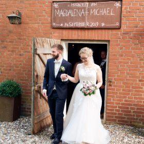 Brautpaar verlässt die Scheune aus rotem Backstein nach der Trauung und tritt in den Sommertag - Hof Wietfeldt Bennebostel © Hochzeitsfotograf www.hochzeitsverliebt.de