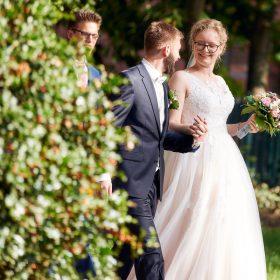 Profil vom schreitenden Brautpaar im Sommer in den Garten der Location - Hof Wietfeldt Bennebostel © Hochzeitsfotograf www.hochzeitsverliebt.de
