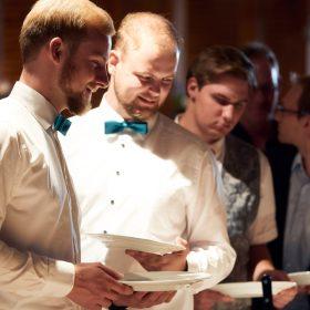Anstehende Hochzeitsgesellschaft mit Tellern in den Händen während der Scheunenhochzeit am Buffet - Hof Wietfeldt Bennebostel © Hochzeitsfotograf www.hochzeitsverliebt.de