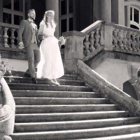Schwarzweissbild vom Hochzeitspaar, das die Steintreppe vom Schloss  herunter kommt - Schloss Eldingen © Hochzeitsfotograf www.hochzeitsverliebt.de