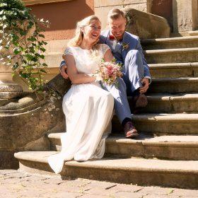 Herzhaft lachende Szene mit dem Paar beim Shooting auf der Treppe  - Schloss Eldingen © Hochzeitsfotograf www.hochzeitsverliebt.de