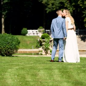 Hände haltend stehen Braut und Bräutigam auf dem Rasen und küssen sich - Schloss Eldingen © Hochzeitsfotograf www.hochzeitsverliebt.de