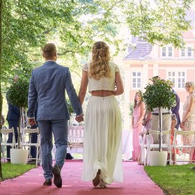 Brautpaar geht auf dem rotem Teppich im Freien zum Traualtar  - Schloss Eldingen © Hochzeitsfotograf www.hochzeitsverliebt.de