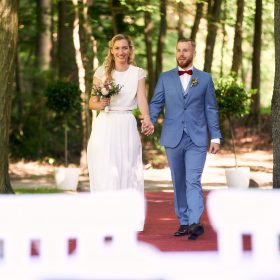 Braut und Bräutigam gehen Hände haltend auf den Trautisch zu © Hochzeitsfotograf www.hochzeitsverliebt.de