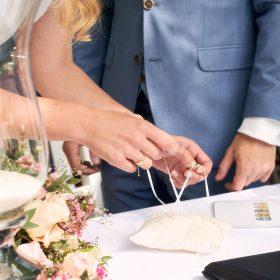 Die Braut fädelt den Ehering vom weissen Schmuckkissen - Schloss Eldingen © Hochzeitsfotograf www.hochzeitsverliebt.de